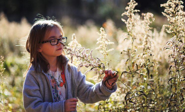 girl-wearing-eyeglasses-smelling-flowers-1634915